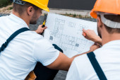 Photo selective focus of builders in helmets looking at blueprint
