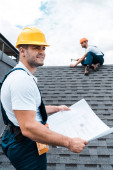 selective focus of handsome builder in helmet holding blueprint near colleague repairing roof