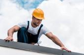 pohledný údržbář ve žluté přilbě a jednotná opravení střechy
