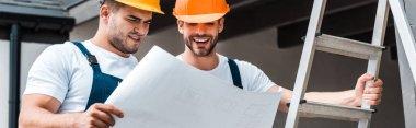 Panoramic shot of happy builders in helmets looking at paper stock vector