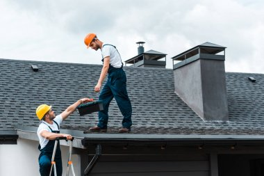 handyman in helmet giving toolbox to handsome colleague standing on rooftop