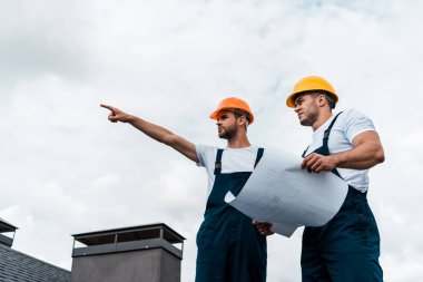 Low angle view of handsome architect pointing with finger near coworker in helmet holding paper stock vector