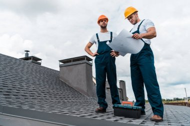 architect standing on roof with hands on hips near coworker with paper