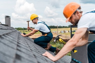 selective focus of handsome handyman repairing roof with colleague