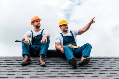 Happy handyman pointing with finger while sitting on rooftop with coworker stock vector
