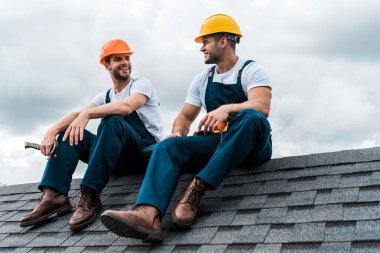 Happy handymen in helmets and uniform sitting on rooftop stock vector