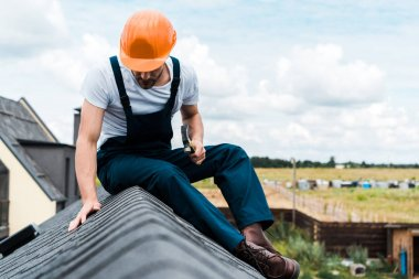 selective focus of handyman in orange helmet sitting on roof and holding hammer