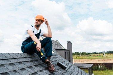 Handsome handyman in orange helmet sitting on roof and holding hammer stock vector