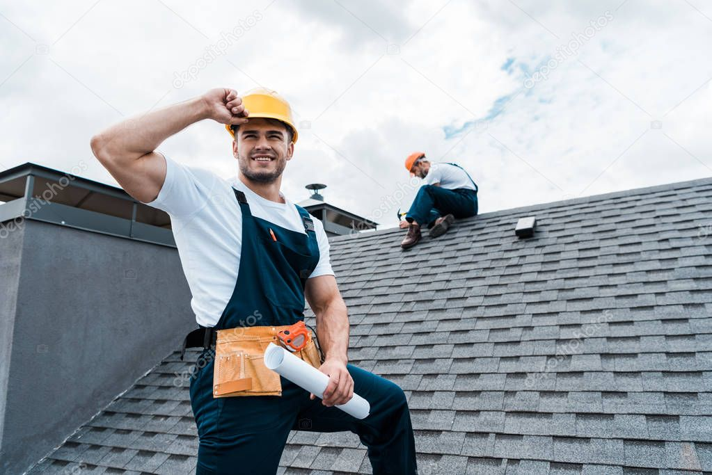 Selective focus of happy repairman holding rolled paper while coworker repairing roof stock vector