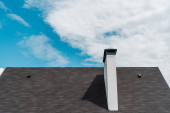 shingles on roof in new luxury house against blue sky with clouds