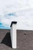 white chimney near shingles on roof in house against blue sky with clouds