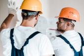 Fotografie selective focus of architect in helmet looking at blueprint near coworker