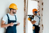 Selektiver Fokus des Heimwerkers, der ein digitales Tablet in der Hand hält, während der Mitarbeiter im Haus arbeitet
