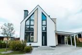 Fotografie Neues Luxus-Haus in der Nähe von grünen Bäumen und Sträuchern auf Gras