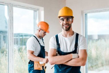 happy repairman in goggles standing with crossed arms near coworker