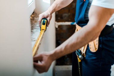cropped view of handyman measuring wall with yellow measuring tape