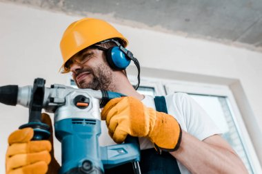 selective focus of handyman in helmet and yellow gloves using hammer drill