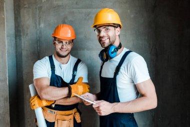 happy repairmen in goggles and helmets standing in house