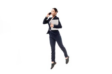 young businesswoman talking on smartphone and holding laptop while dancing isolated on white