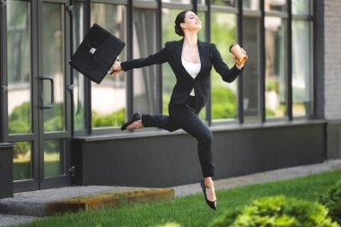 happy businesswoman levitating while holding briefcase and coffee to go