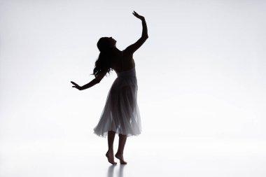 graceful, elegant ballerina in white dress dancing on grey background