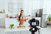 selective focus of attractive video blogger gesturing near fruits and digital camera
