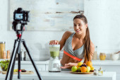 Photo selective focus of cheerful sportswoman preparing smoothie in blender