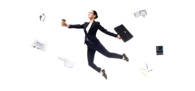 panoramic shot of businesswoman holding coffee to go and briefcase while levitating surrounded headphones, newspaper, calculator and stationery isolated on white