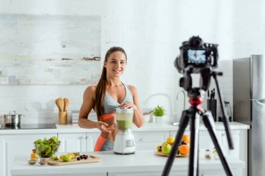 Selective focus of cheerful woman near blender with smoothie stock vector