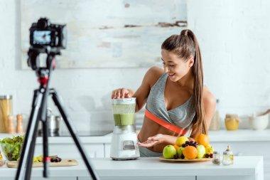 Selective focus of cheerful girl preparing smoothie in blender stock vector