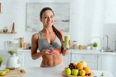 Photo selective focus of cheerful girl with sportswear gesturing and holding glass with tasty smoothie
