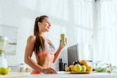 Photo low angle view of attractive and happy woman holding glass with green smoothie