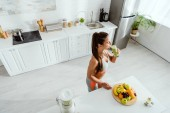 Photo overhead view of woman drinking smoothie near fruits in kitchen
