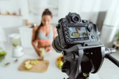 selective focus of digital camera with girl holding smoothie on screen