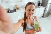 Fotografie selective focus of smiling girl holding glass with green smoothie and looking at camera