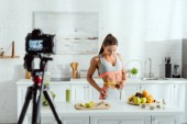 Photo selective focus of girl measuring waist near fruits and