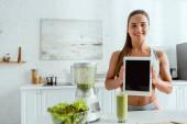 glückliche Frau mit digitalem Tablet mit leerem Bildschirm in der Nähe von Mixer und Glas mit Smoothie