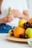 selective focus of ripe delicious fruits near girl