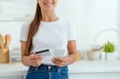 oříznutý pohled šťastné ženy držící telefon Smartphone a kreditní karty