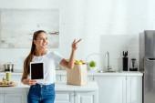Fotografie fröhliches Mädchen, das ein digitales Tablet mit leerem Bildschirm in der Hand hält und mit dem Finger auf Lebensmittel zeigt