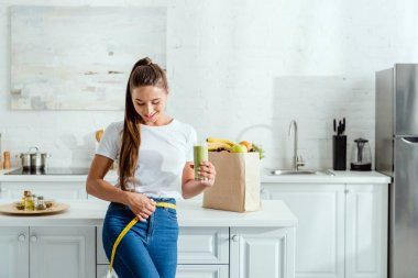 happy young woman measuring waist and holding glass with smoothie near groceries
