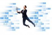 Photo young businesswoman using laptop while levitating near e-mail icons isolated on white