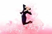 Fotografia giovane imprenditrice che ascolta la musica in cuffia mentre salta su sfondo con note musicali e spruzzi di fumo rosa isolati sul bianco