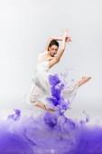 beautiful ballerina in white dress dancing near blue paint splashes on grey back ground