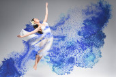 young ballerina in white dress dancing in blue paint splashes on grey background