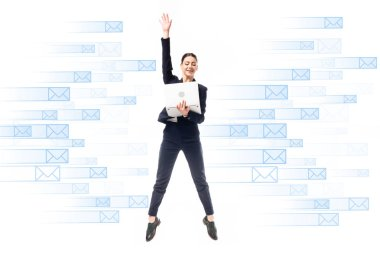 Smiling businesswoman using laptop while jumping on background with e-mail icons isolated on white stock vector