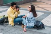 Dvourasový muž sedící na schodech a fotografovat ženu v brýlích s batohu