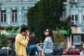 Dvourasový muž, který sedí a fotografovat ženu v brýlích s batohu