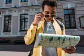 Photo Bi-racial man in sunglasses with backpack looking at map in his hand