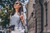 Šťastná žena v brýlích s batohu na ruce s digitálním fotoaparátem